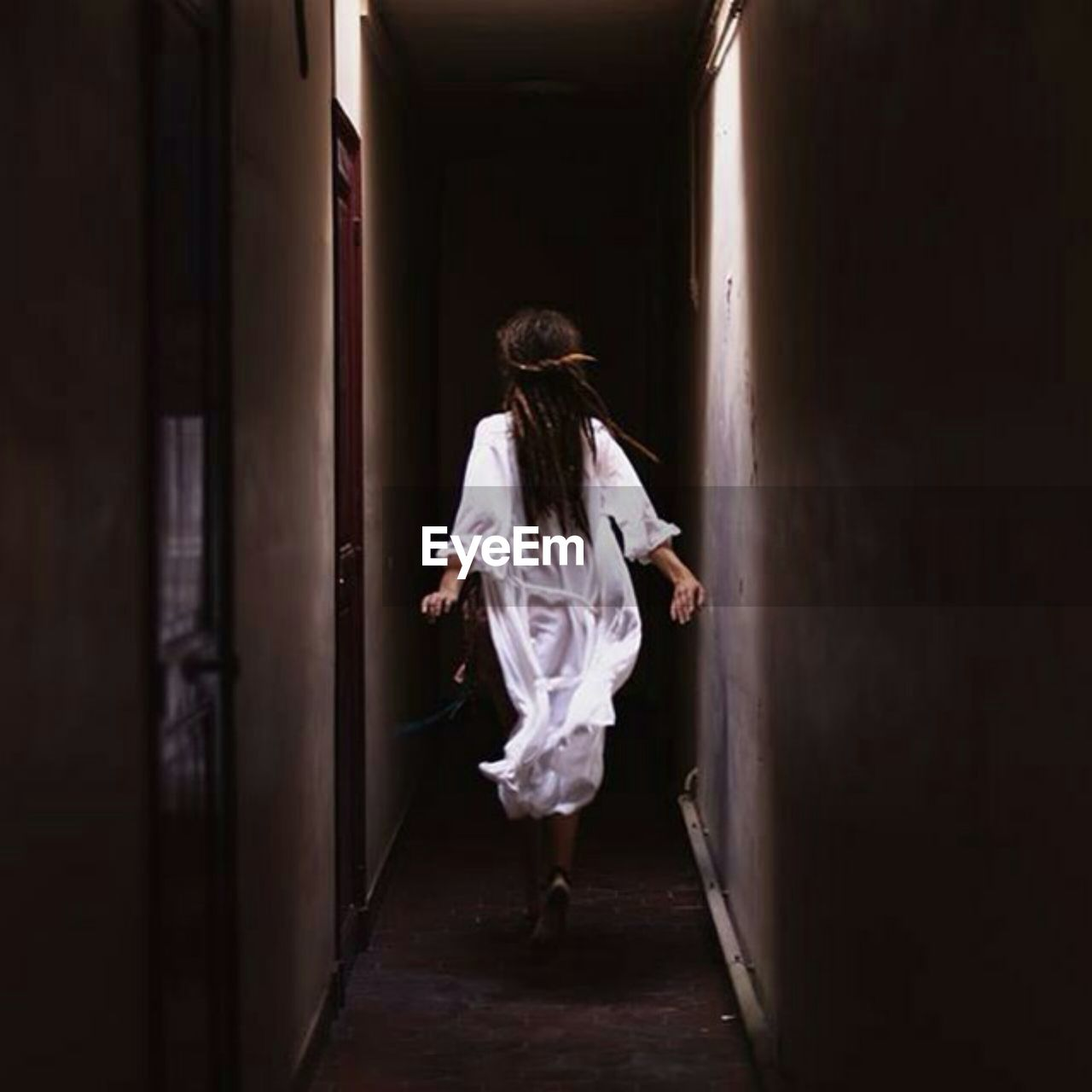full length, one person, rear view, indoors, adult, fear, corridor, arcade, walking, horror, spooky, entrance, mystery, hairstyle, building, door, women, emotion, leaving, ghost