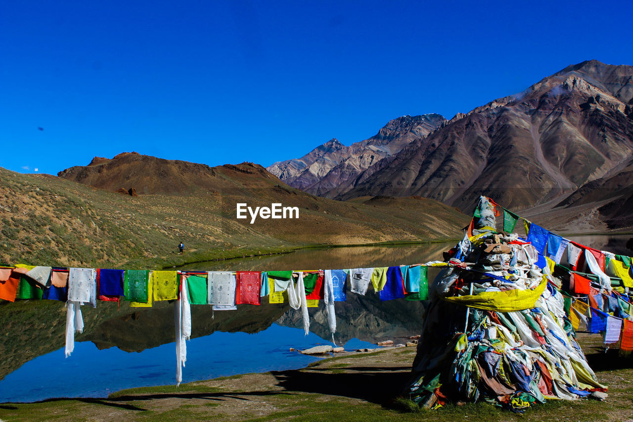 multi colored, mountain, sky, hanging, blue, mountain range, nature, no people, clear sky, flag, day, religion, scenics - nature, copy space, belief, tranquility, textile, sunlight, clothing, drying, outdoors