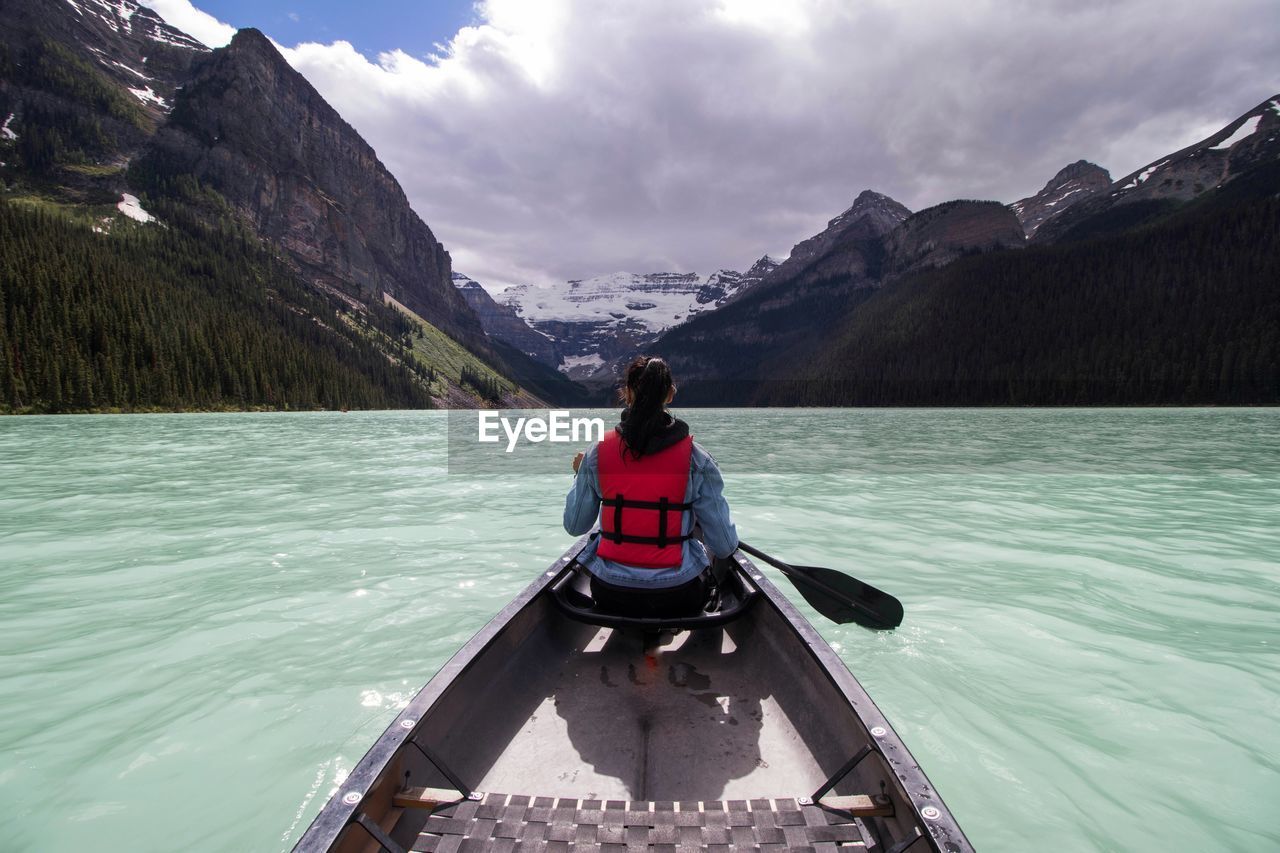 Rear View Of Woman Rowing Rowboat In Lake Towards Mountains