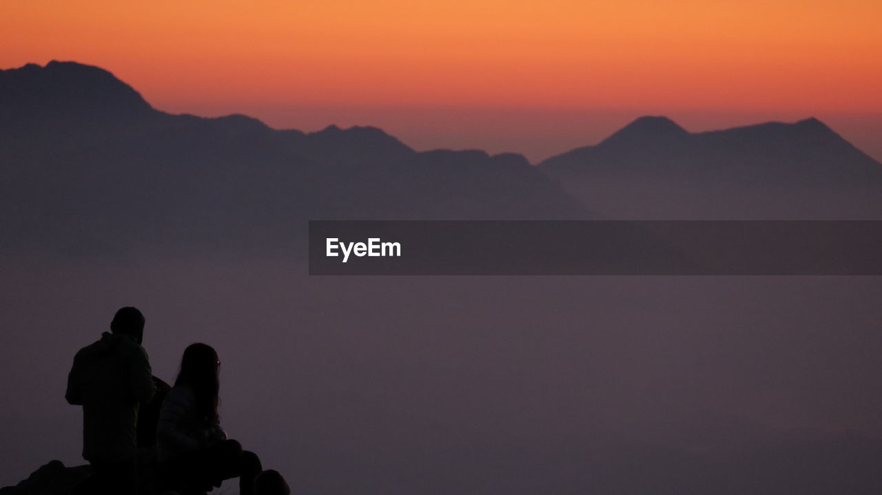 Man and woman against mountains during sunset