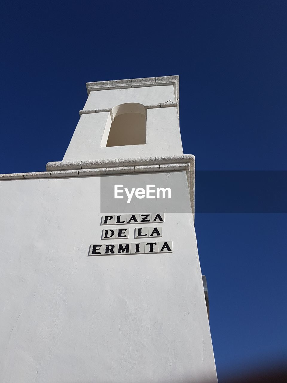 Low Angle View Of Text On Building Against Clear Blue Sky