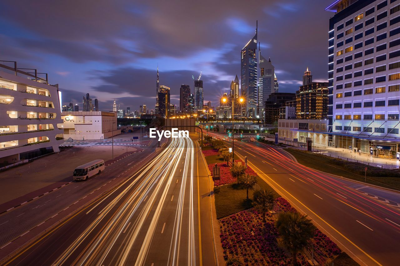 building exterior, built structure, architecture, city, illuminated, long exposure, motion, street, road, light trail, transportation, sky, night, city life, speed, building, blurred motion, nature, office building exterior, no people, cityscape, city street, skyscraper, outdoors