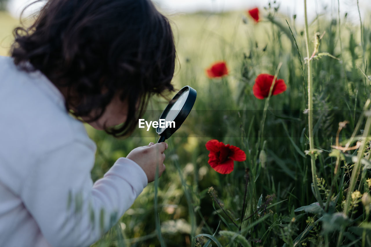 Rear view of girl looking at flower through magnifying glass