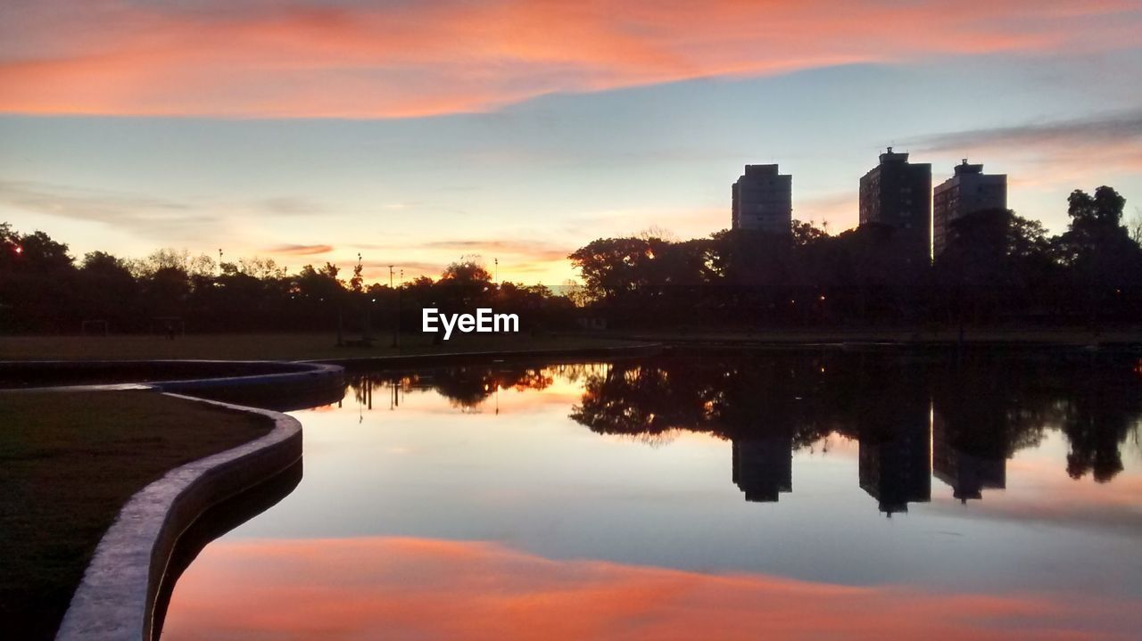 sunset, sky, reflection, cloud - sky, architecture, water, built structure, building exterior, tree, city, silhouette, skyscraper, waterfront, no people, outdoors, scenics, modern, travel destinations, beauty in nature, nature, cityscape, urban skyline, day