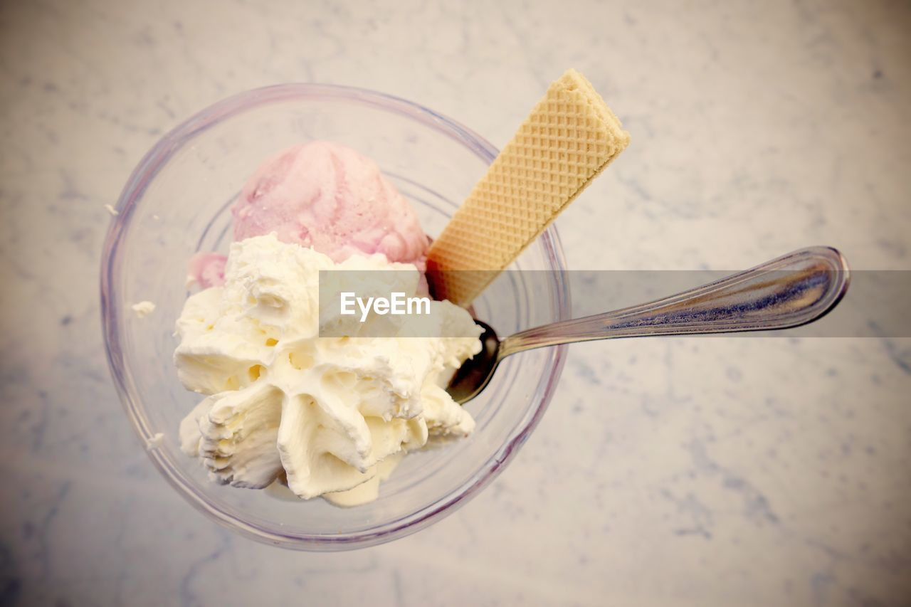 spoon, kitchen utensil, eating utensil, food, food and drink, ice cream, frozen food, frozen, dairy product, table, indoors, freshness, indulgence, high angle view, close-up, still life, sweet food, no people, sweet, bowl, temptation