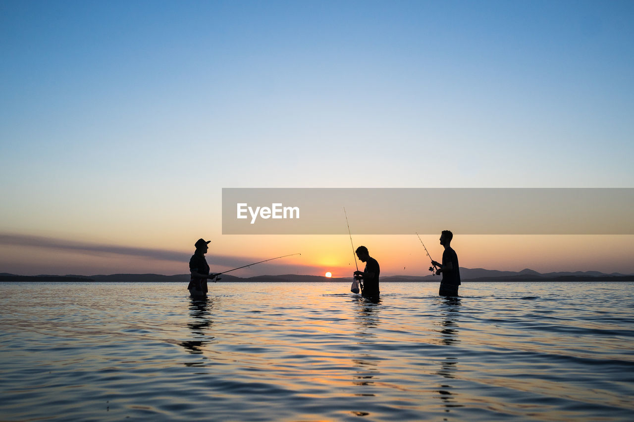 Silhouette men fishing in sea against sky during sunset