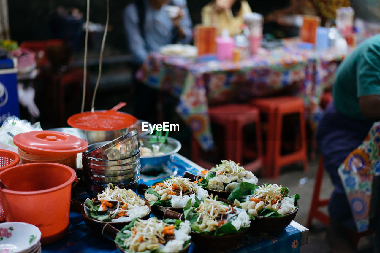 food and drink, food, freshness, real people, business, incidental people, table, focus on foreground, wellbeing, choice, healthy eating, market, ready-to-eat, variation, retail, vegetable, market stall, day, container, indoors, glass, retail display