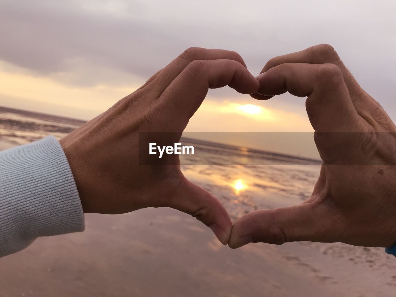 Cropped Image Of Hands Making Heart Shape Against Sea During Sunset