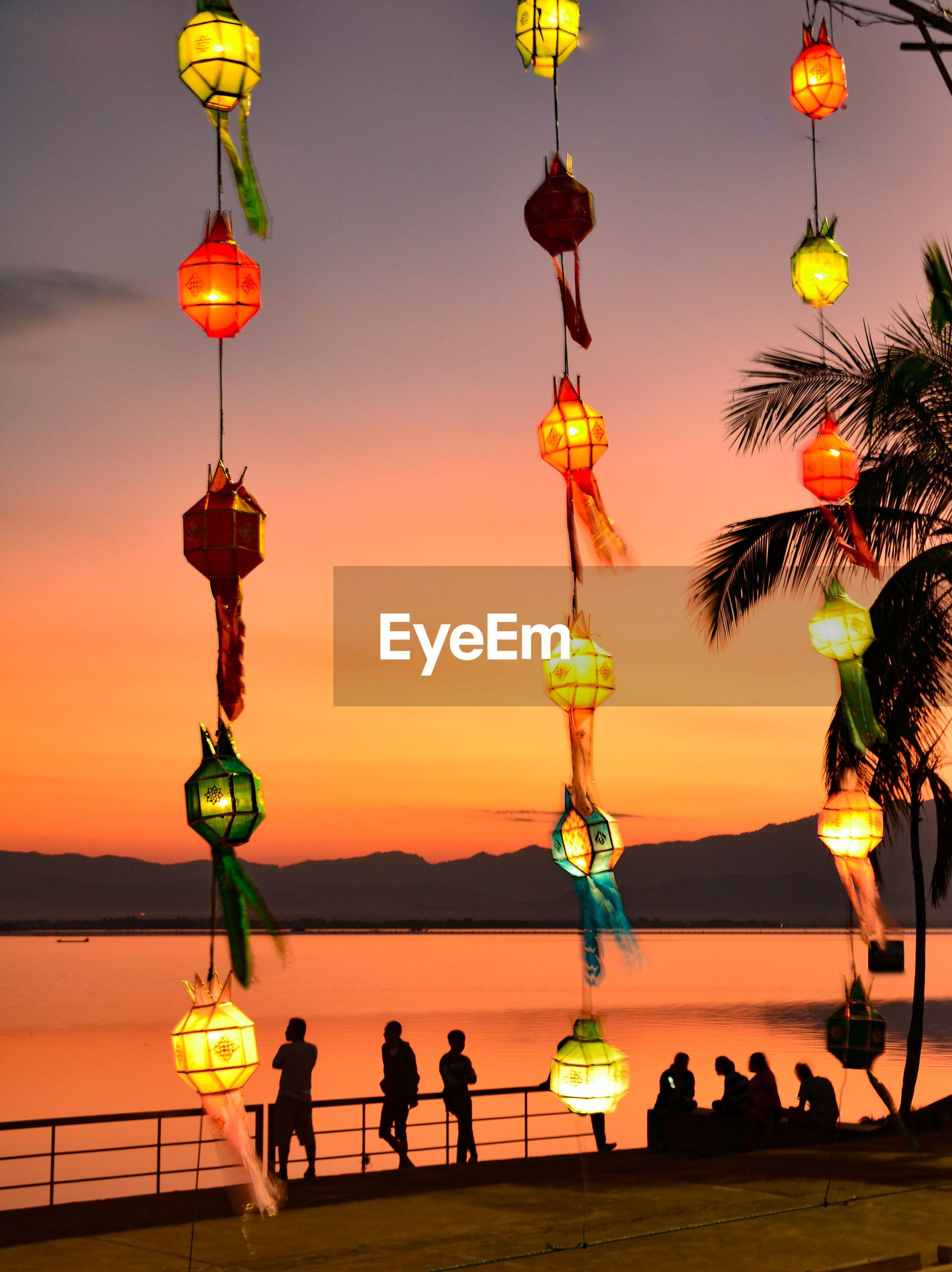 Illuminated lanterns hanging against sky during sunset