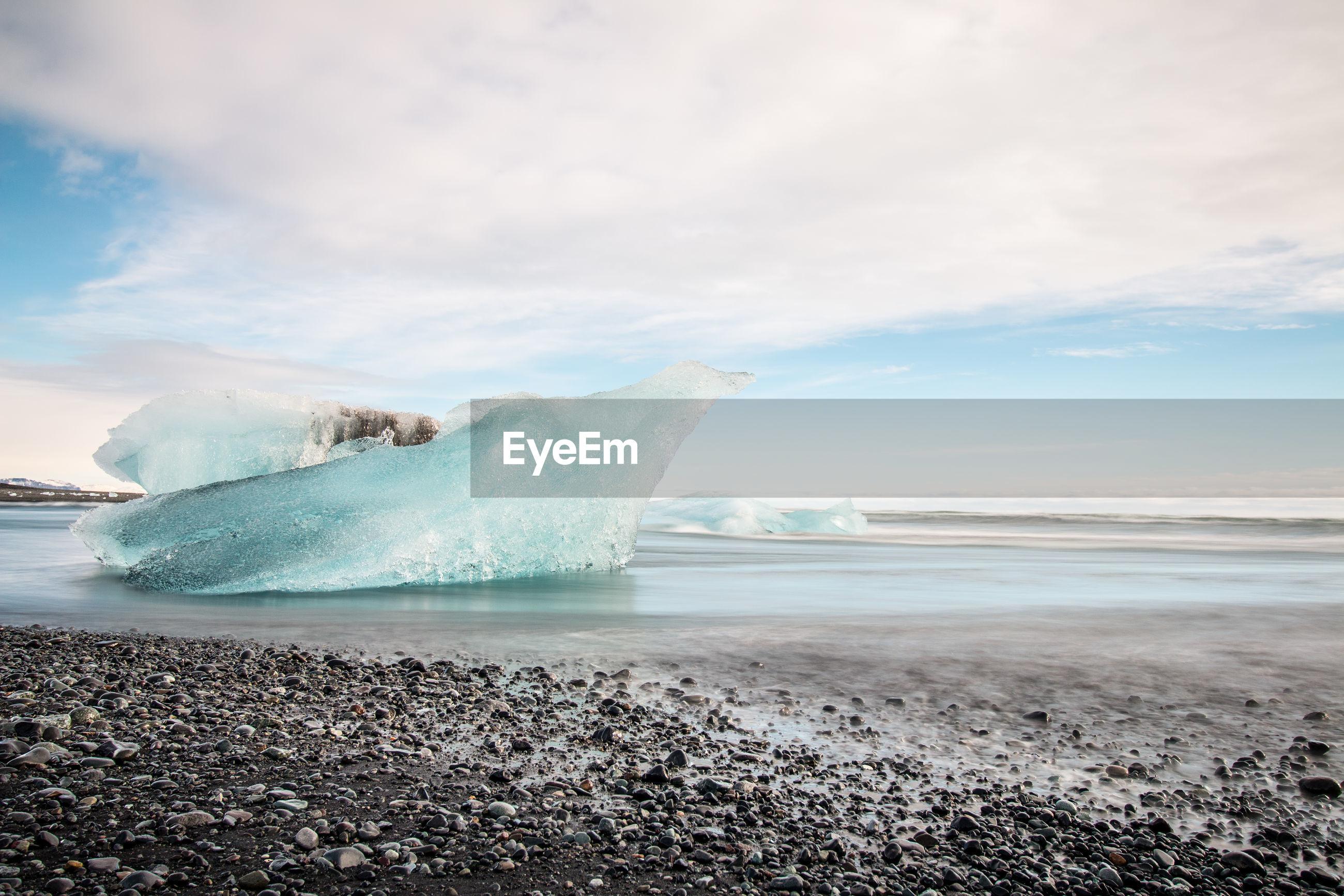 Icebergs at beach against cloudy sky