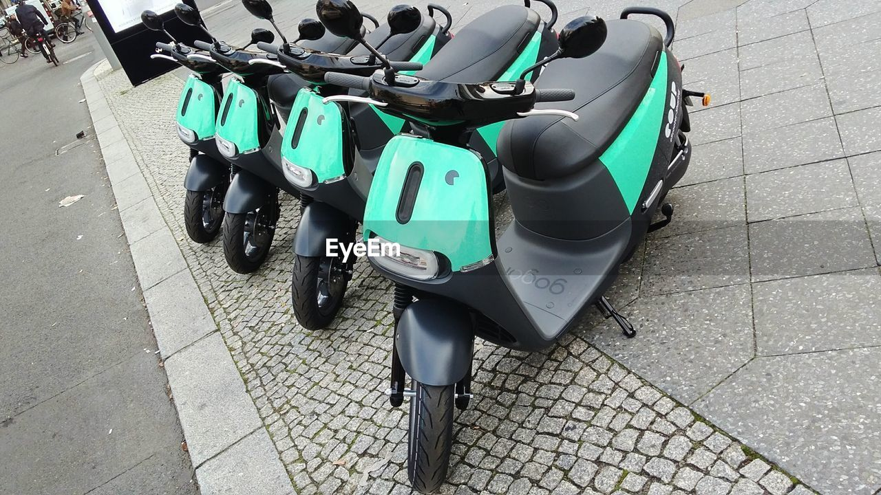 transportation, stationary, day, in a row, land vehicle, mode of transport, outdoors, high angle view, large group of objects, no people, sidewalk, scooter, bicycle rack