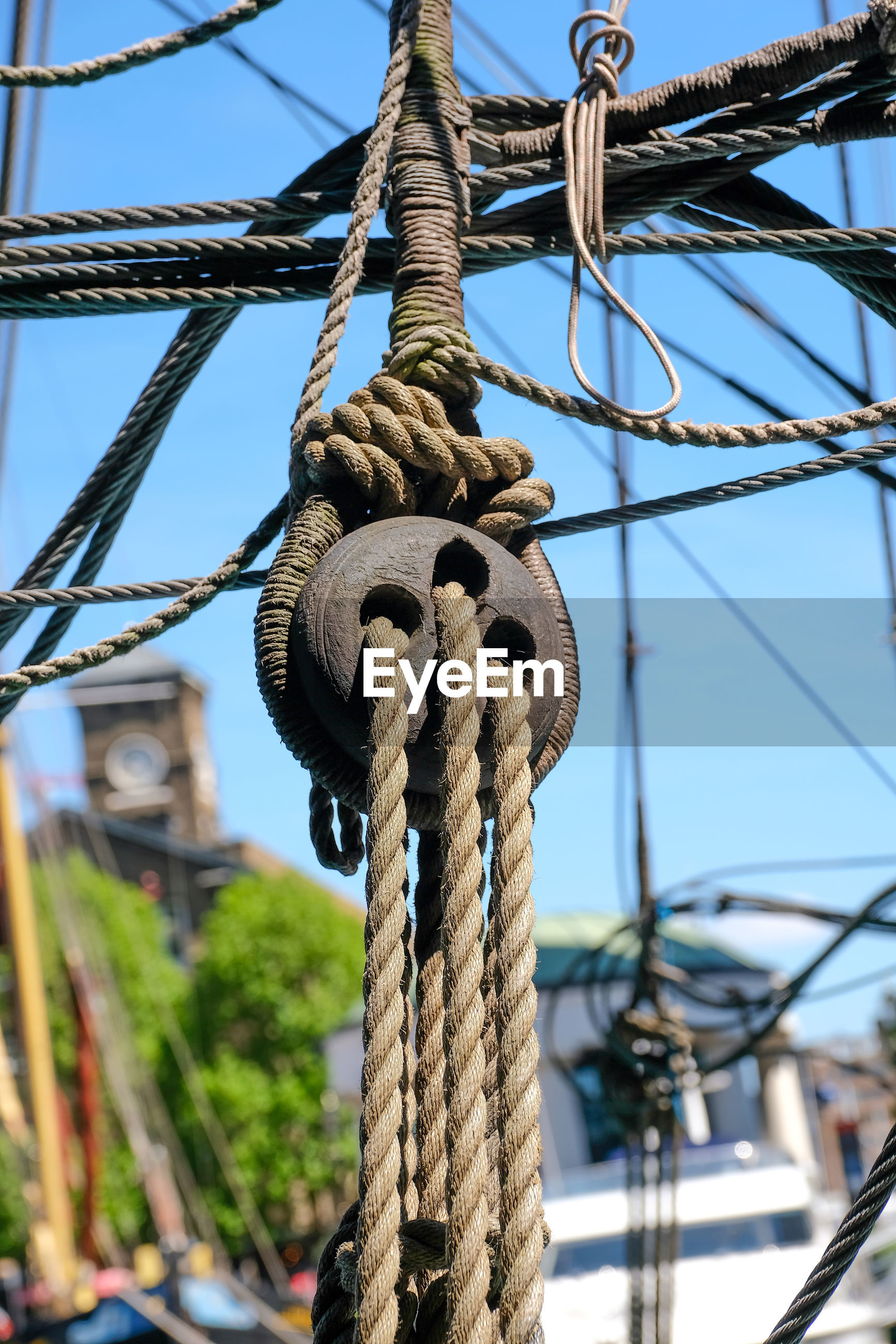 Low angle view of rope on pulley against clear blue sky