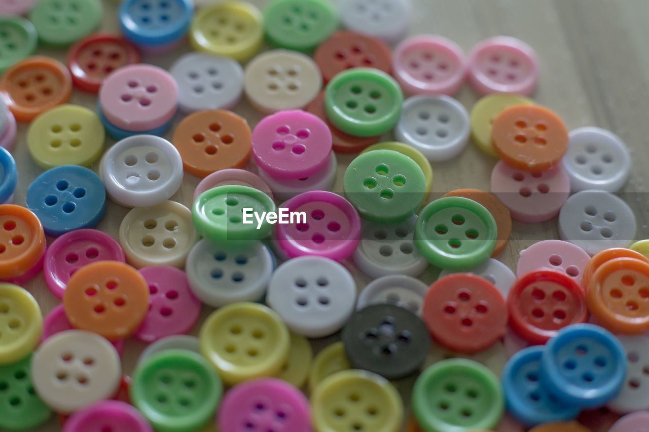 multi colored, large group of objects, choice, variation, button, still life, no people, indoors, close-up, thread, high angle view, abundance, shape, backgrounds, plastic, table, full frame, sewing item, geometric shape, stack, needlecraft product, spool