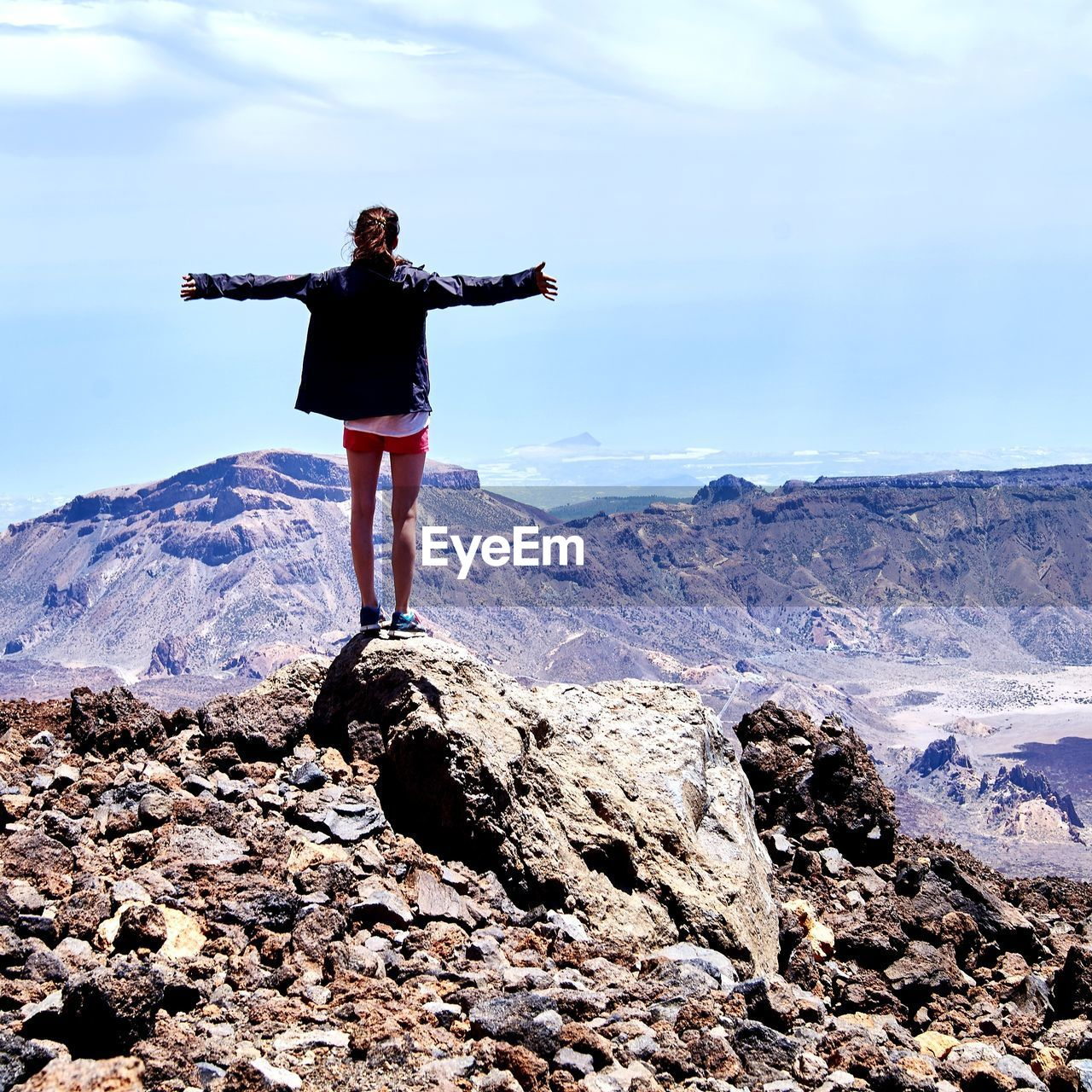 Rear view of woman arms outstretched standing on rock against sky
