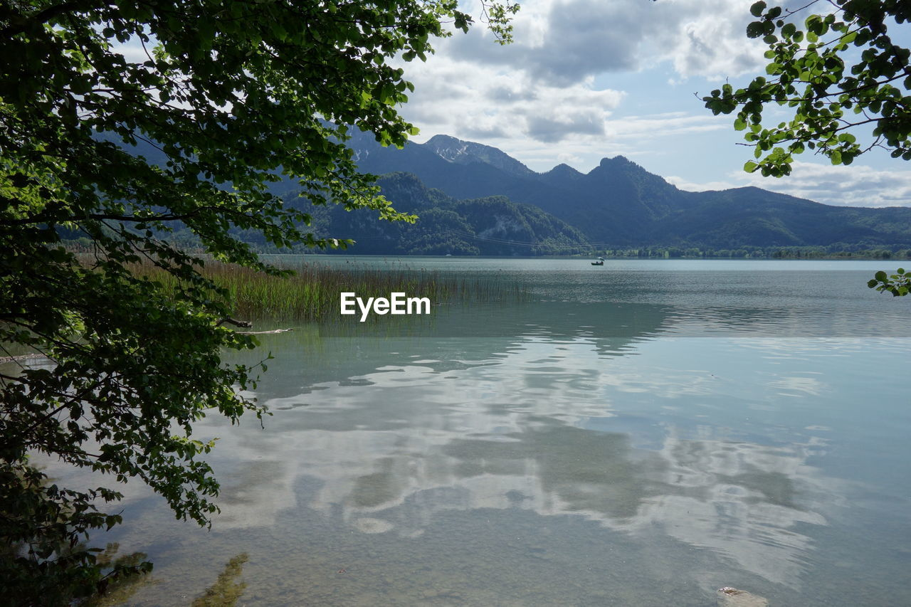 water, mountain, cloud - sky, scenics - nature, sky, tranquil scene, beauty in nature, tree, tranquility, lake, reflection, plant, nature, mountain range, day, non-urban scene, idyllic, no people, waterfront, outdoors
