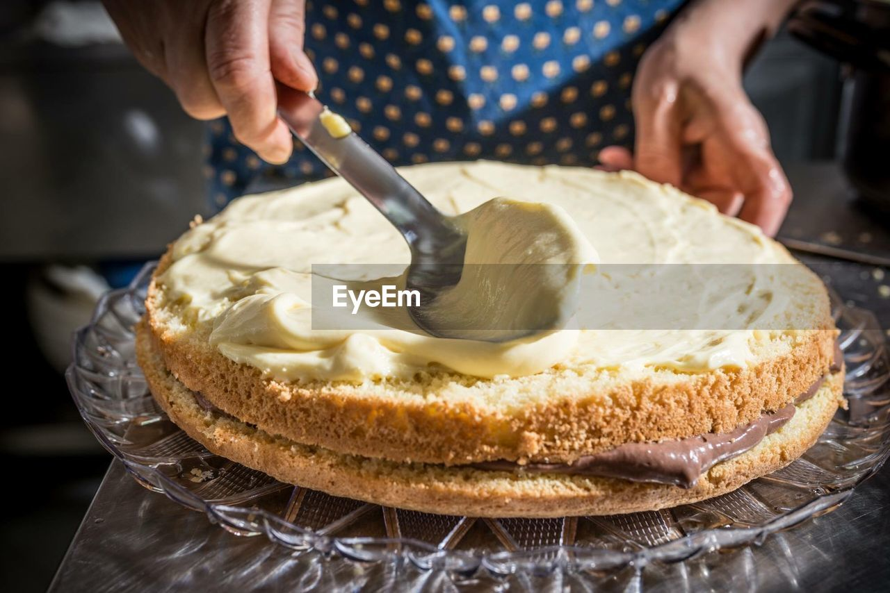 Midsection Of Woman Making Cake At Home