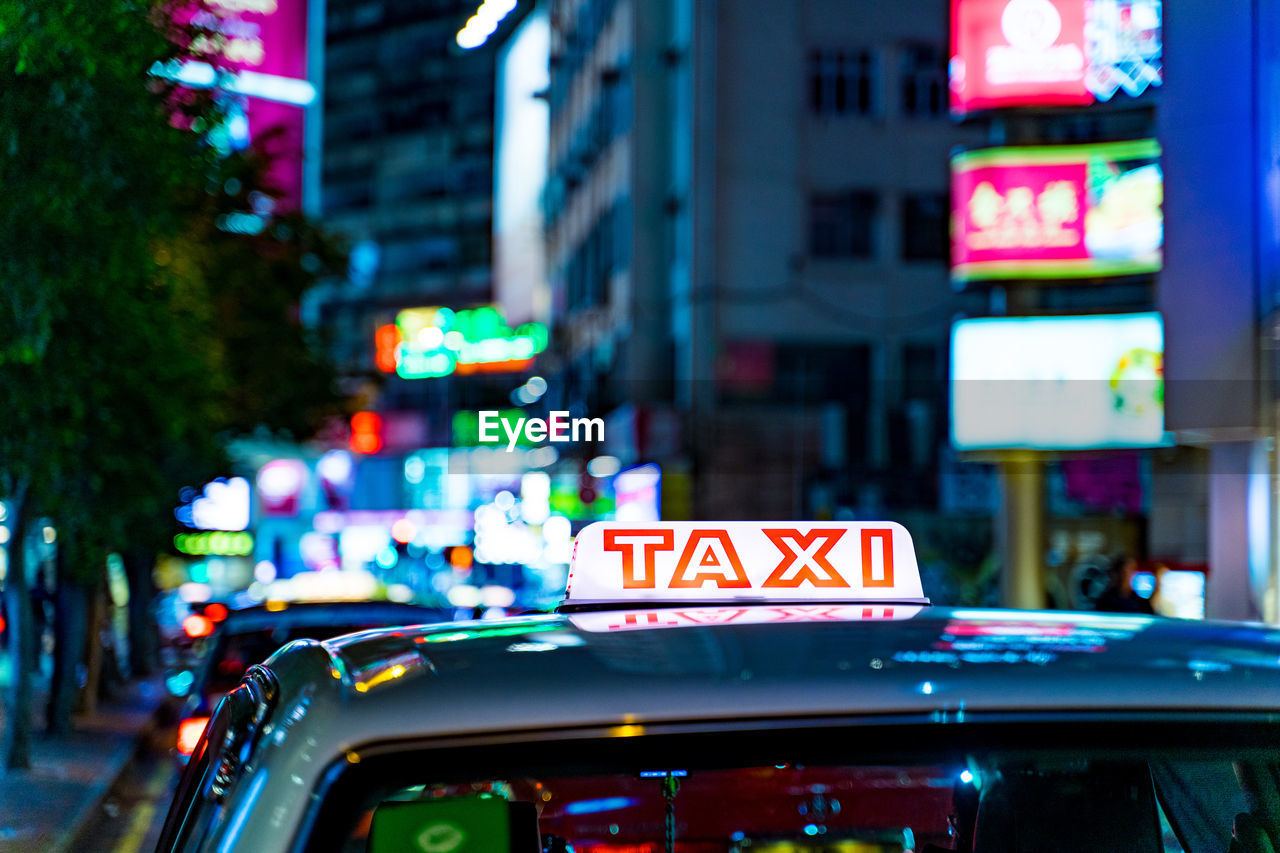 city, car, illuminated, mode of transportation, motor vehicle, architecture, transportation, building exterior, street, communication, focus on foreground, text, night, taxi, neon, built structure, city life, sign, land vehicle, road, outdoors