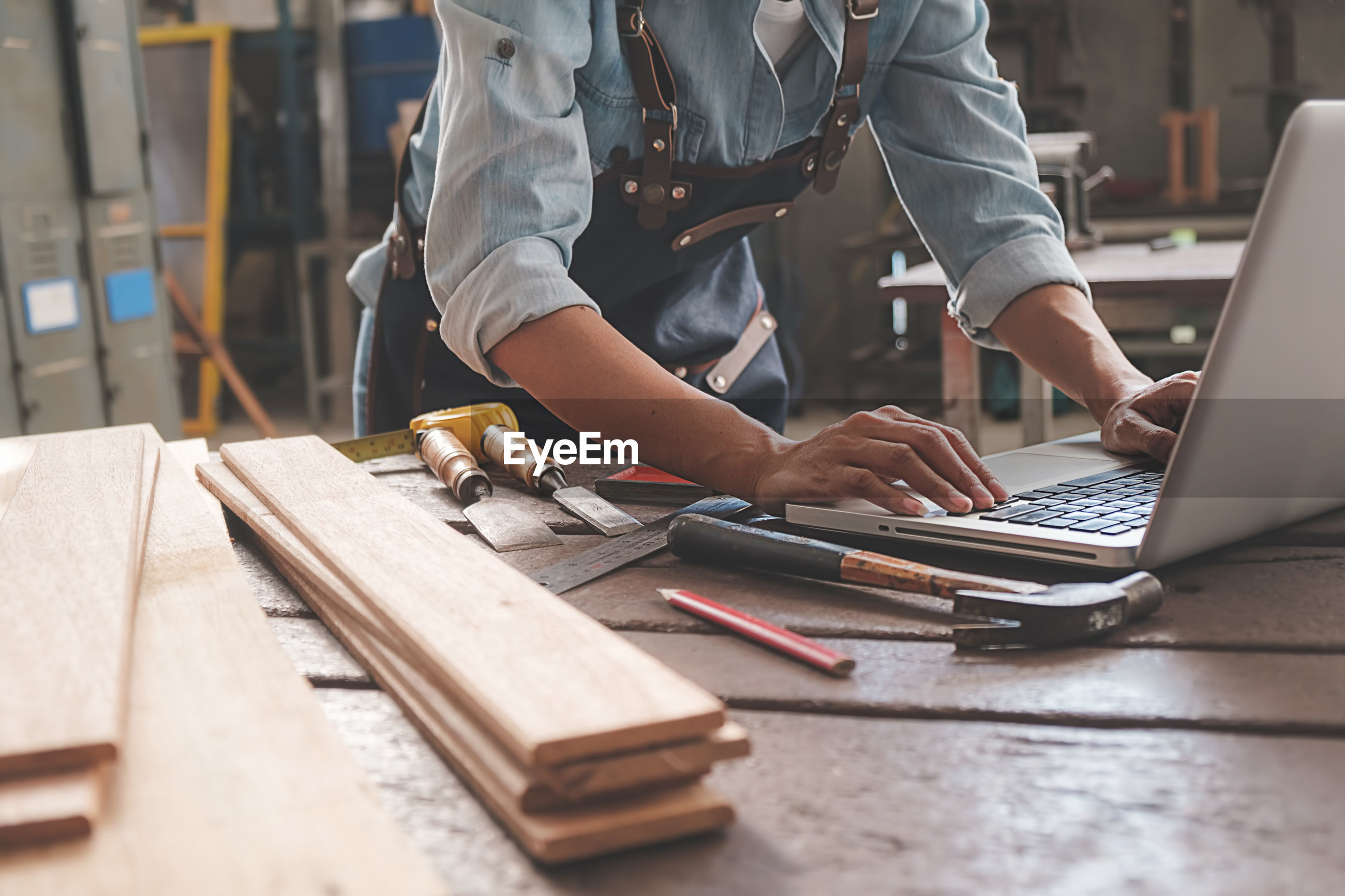 Midsection of carpenter using laptop on table in workshop