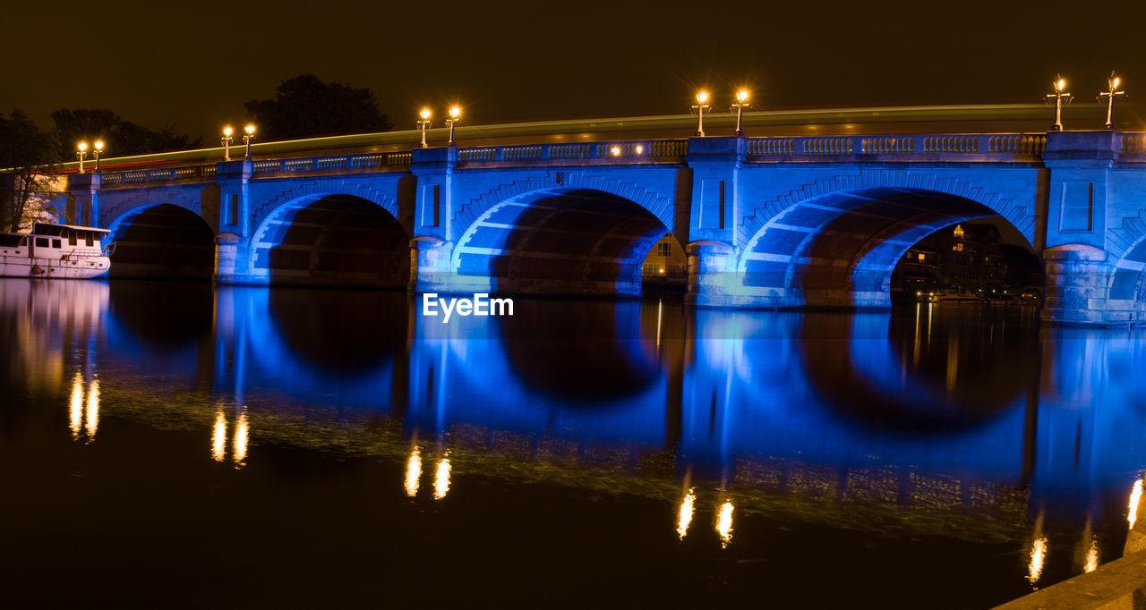 REFLECTION OF ILLUMINATED BRIDGE OVER RIVER AGAINST SKY