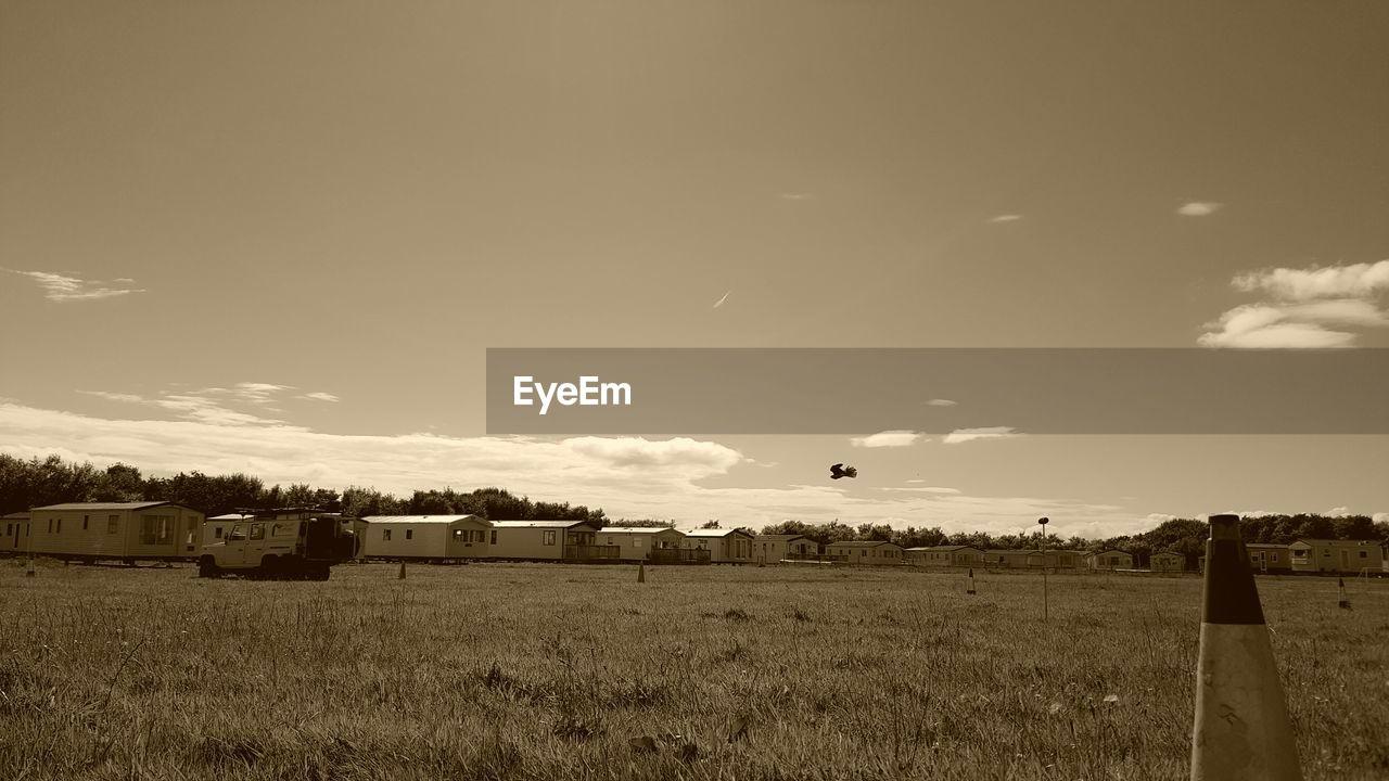 Farm House And Grass Field Against Sky