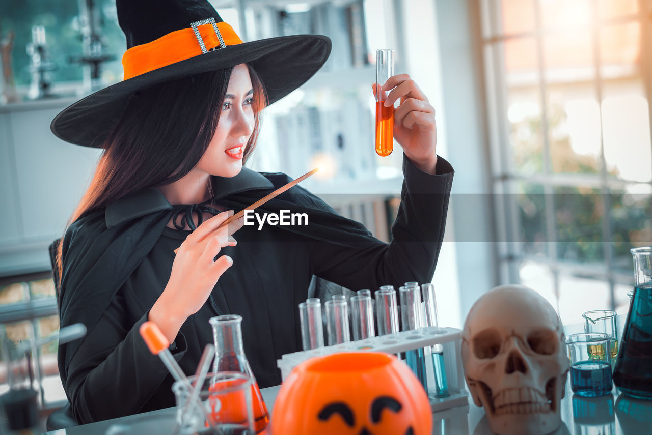 real people, one person, women, young women, young adult, lifestyles, indoors, orange color, clothing, hat, holding, table, focus on foreground, leisure activity, front view, business, waist up, day, hairstyle, glass