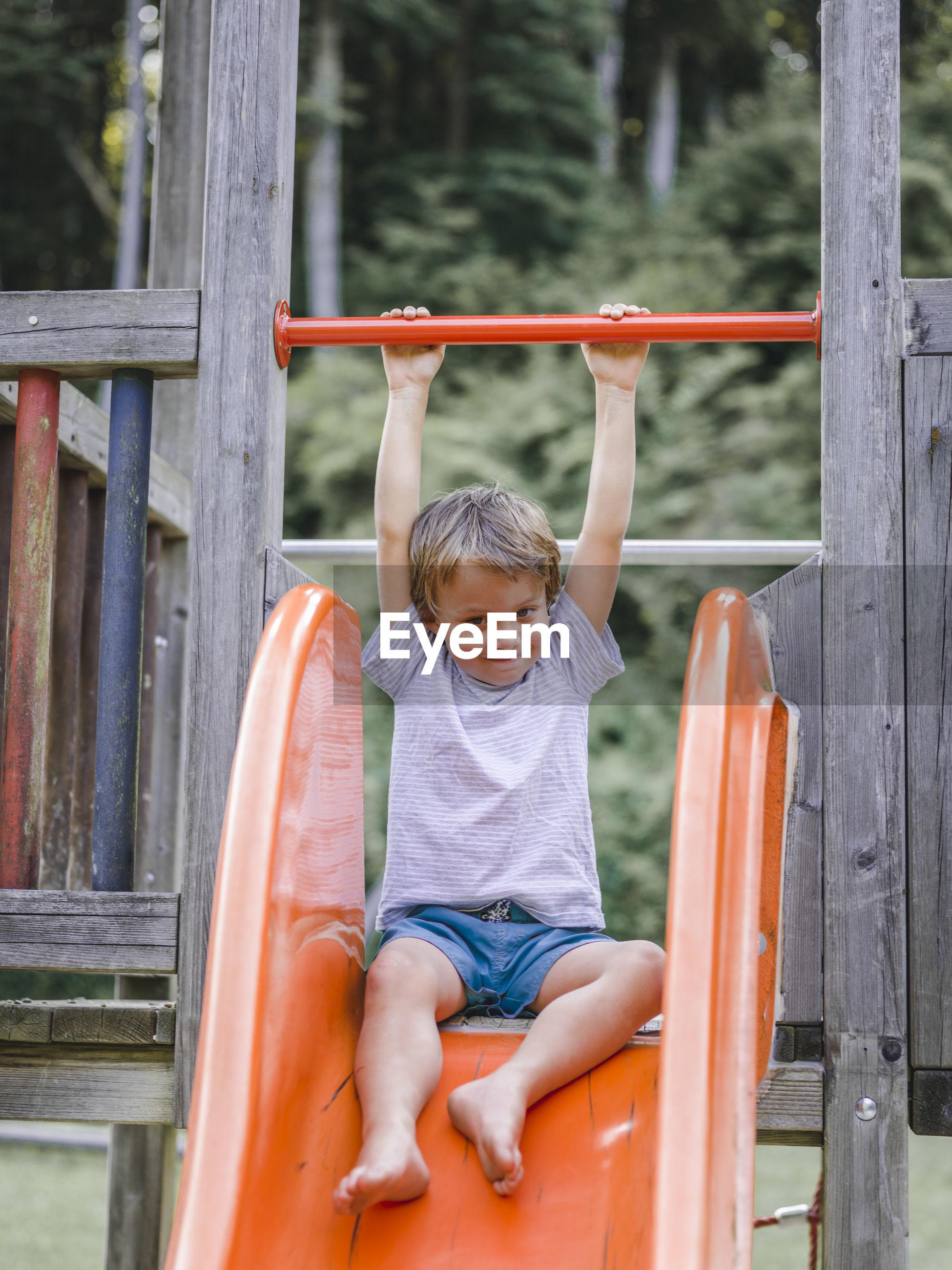 Full length of boy enjoying on slide at playground