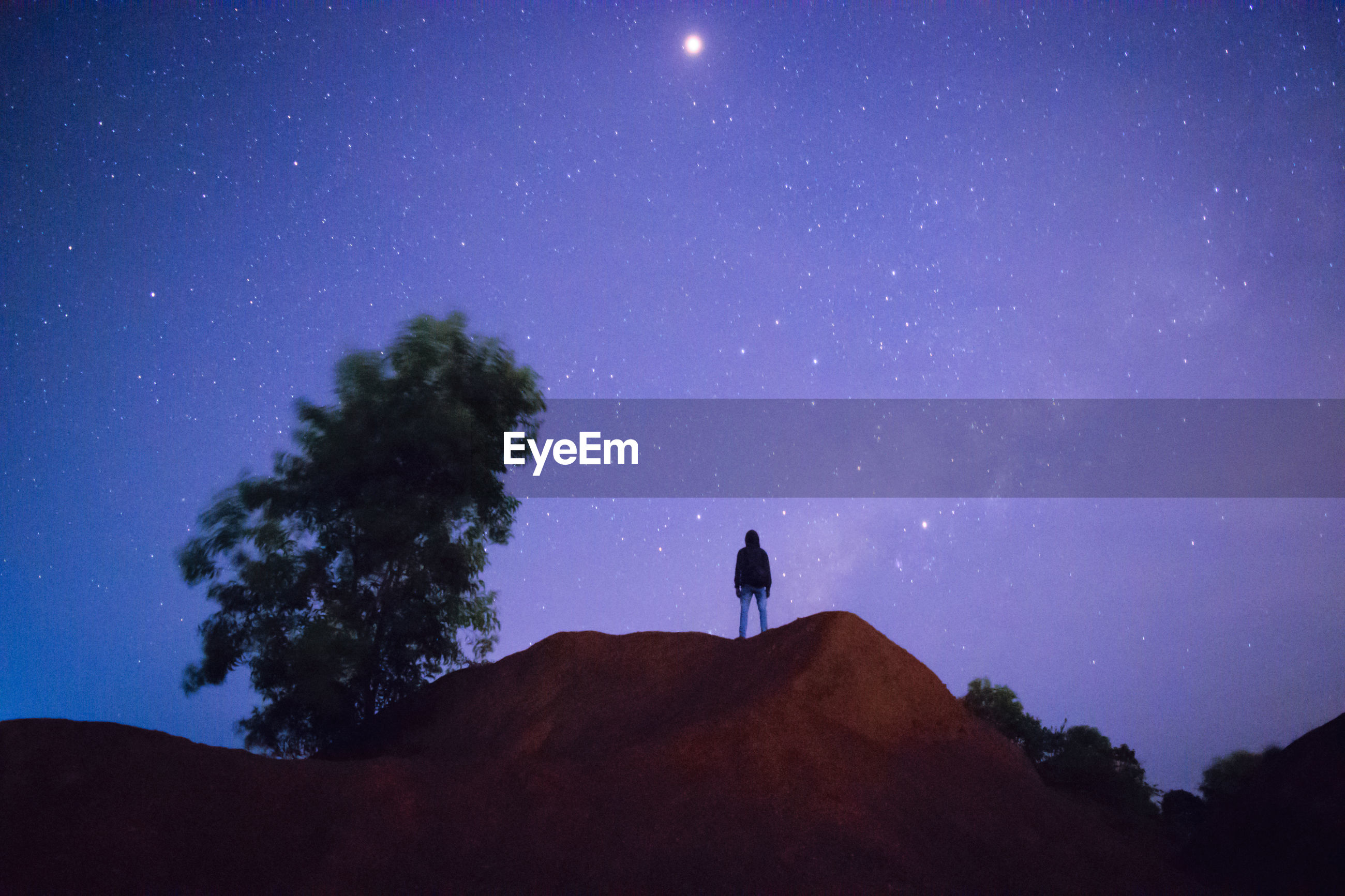Low angle view of silhouette mid adult man standing on mountain against star field at night