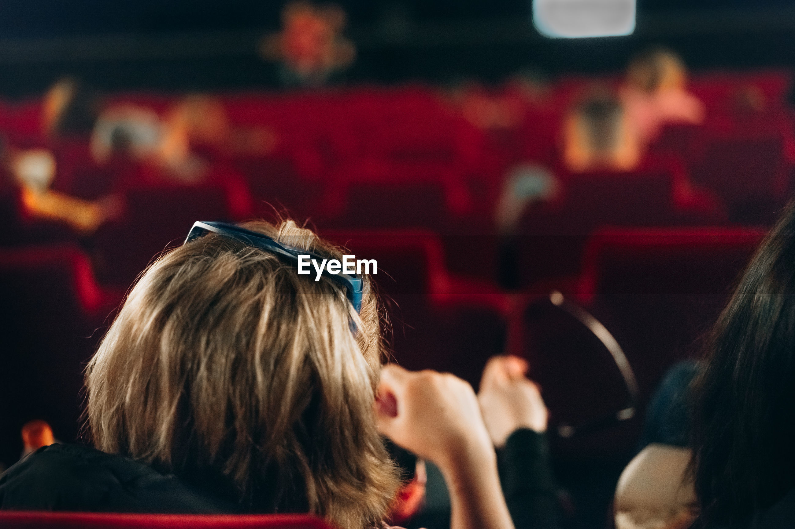 Rear view of woman with friend sitting at theater