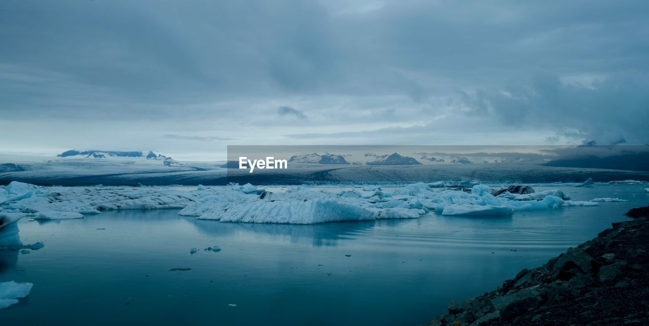 Scenic View Of Ice Berg In Sea Against Sky