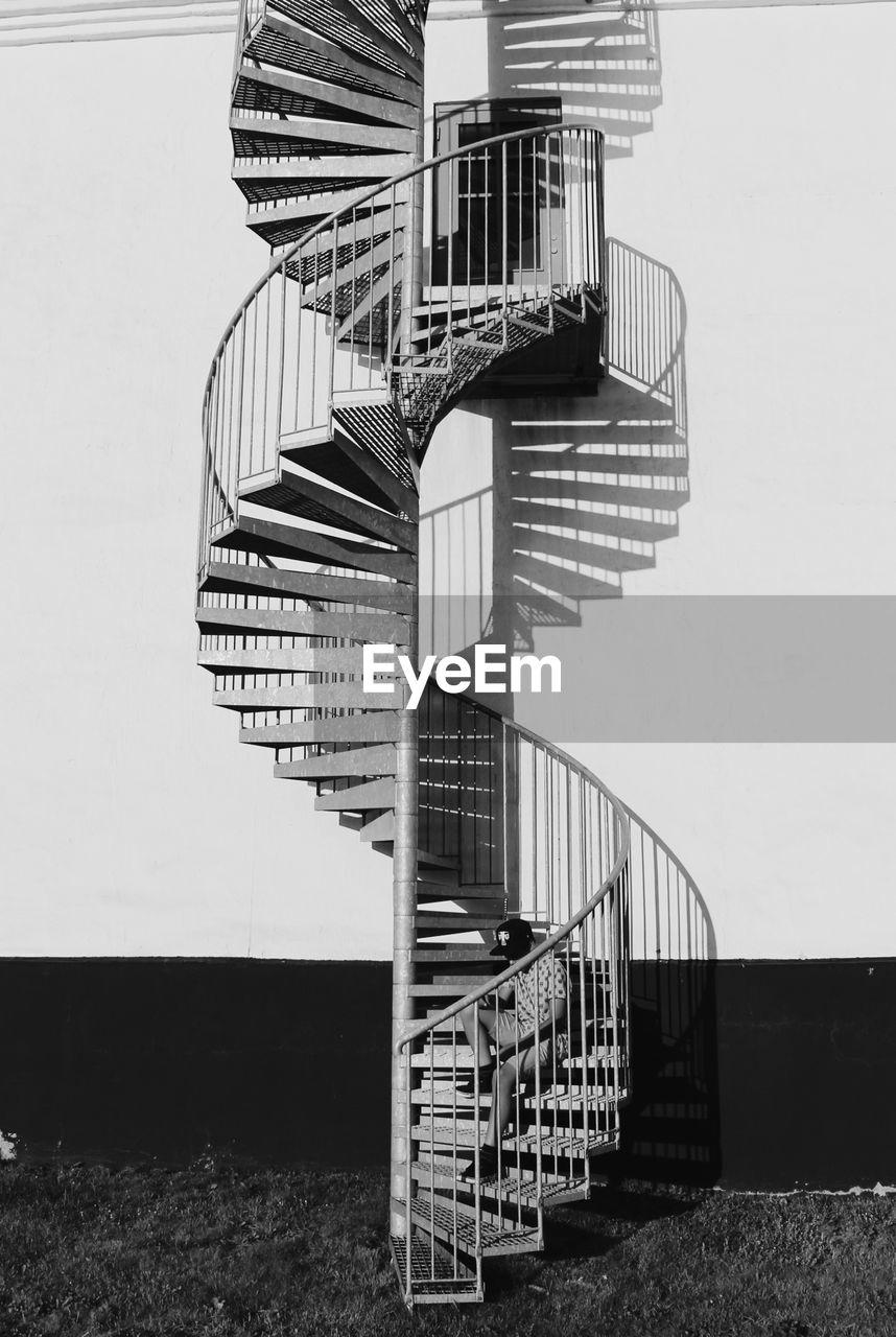 Man Sitting On Spiral Staircase
