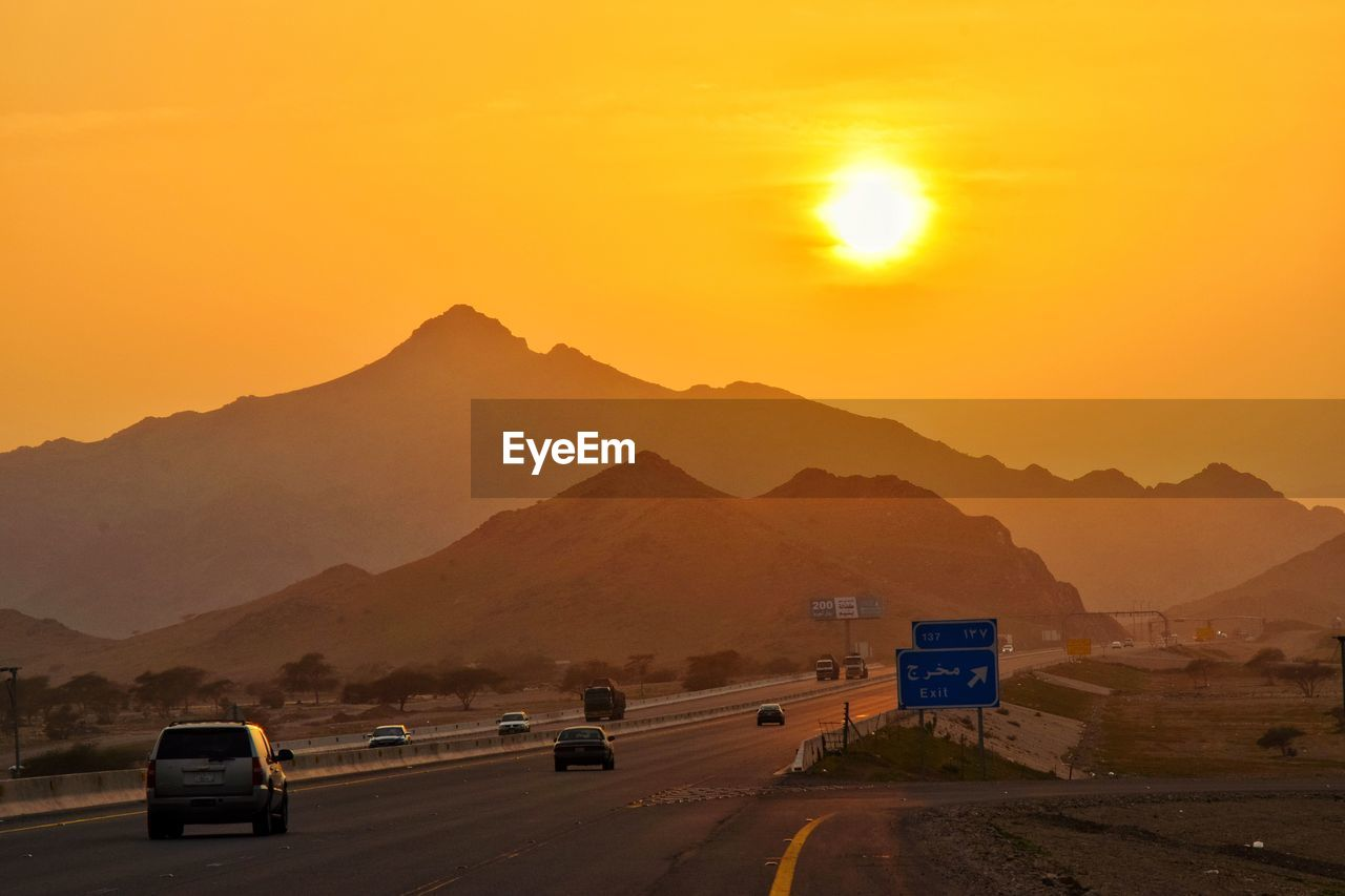 transportation, mountain, road, mode of transportation, sky, motor vehicle, land vehicle, car, sunset, mountain range, orange color, sun, nature, beauty in nature, scenics - nature, direction, the way forward, no people, non-urban scene, sign, outdoors, road trip