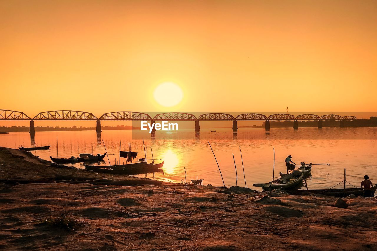 sunset, sky, orange color, water, nautical vessel, transportation, beauty in nature, silhouette, sun, mode of transportation, nature, scenics - nature, sea, real people, beach, idyllic, tranquil scene, architecture, tranquility