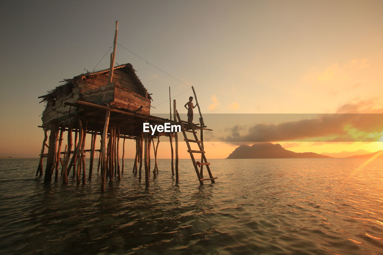 BUILT STRUCTURE ON SEA AGAINST SKY DURING SUNSET