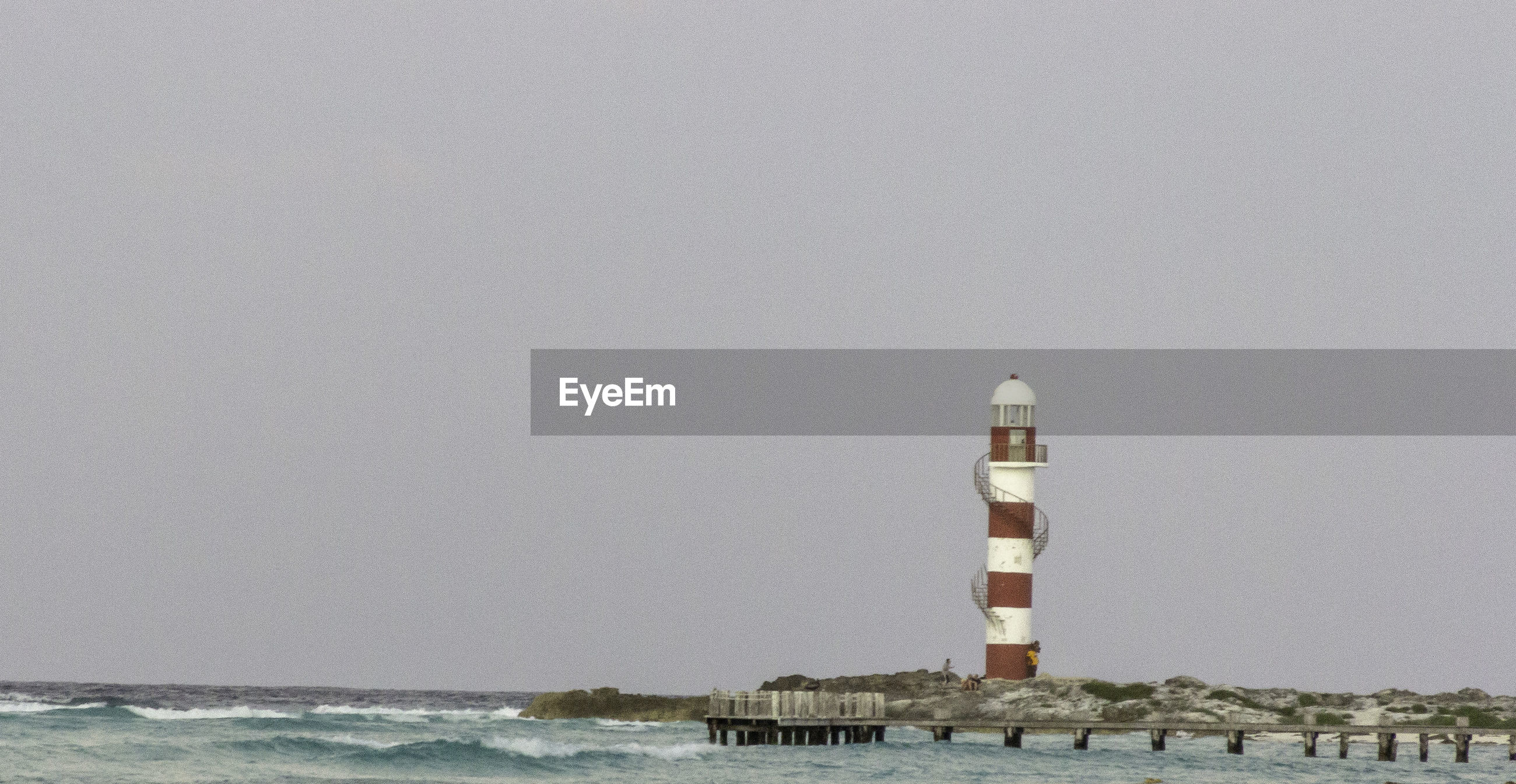 Lighthouse by sea against clear sky | ID: 139867101