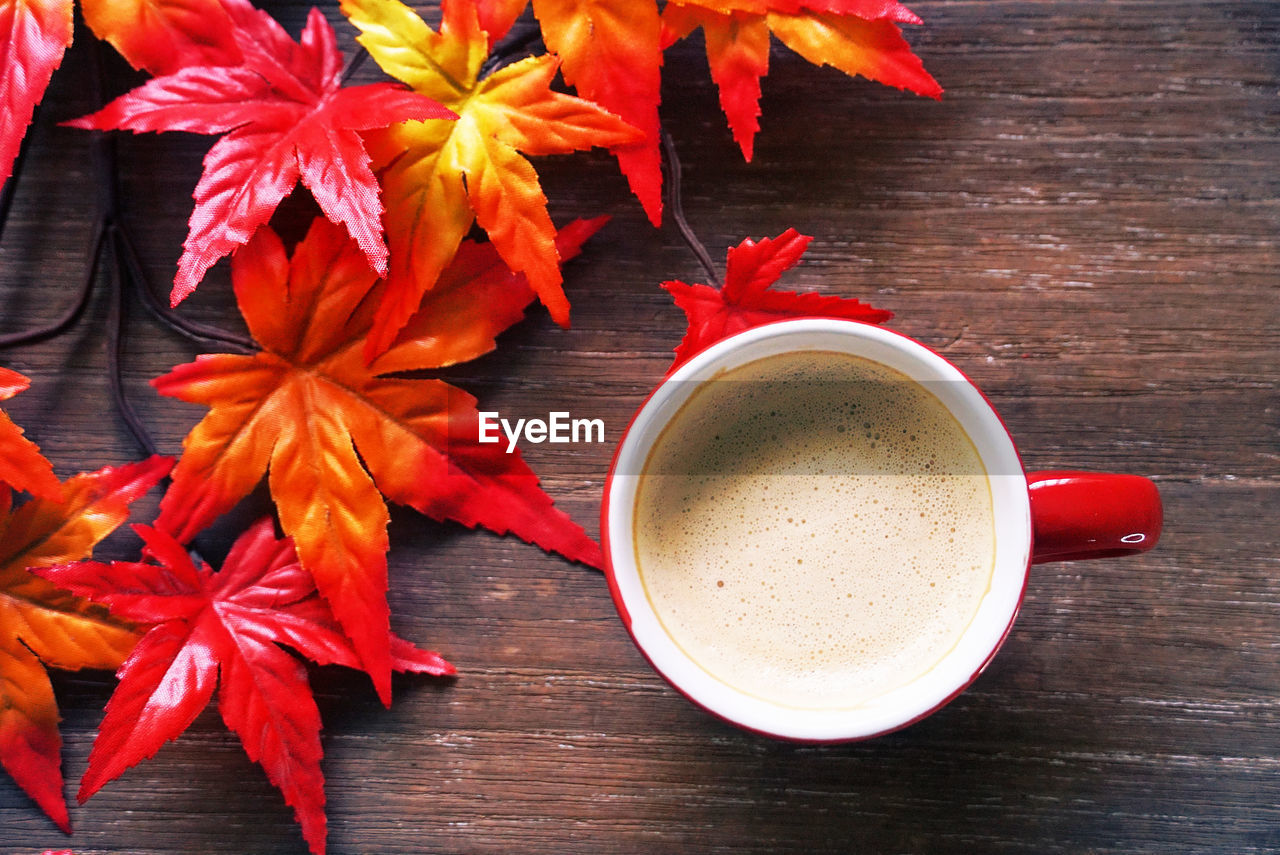 table, food and drink, freshness, drink, indoors, refreshment, still life, wood - material, red, high angle view, leaf, orange color, plant part, coffee - drink, coffee cup, cup, coffee, close-up, mug, directly above, no people, leaves, maple leaf
