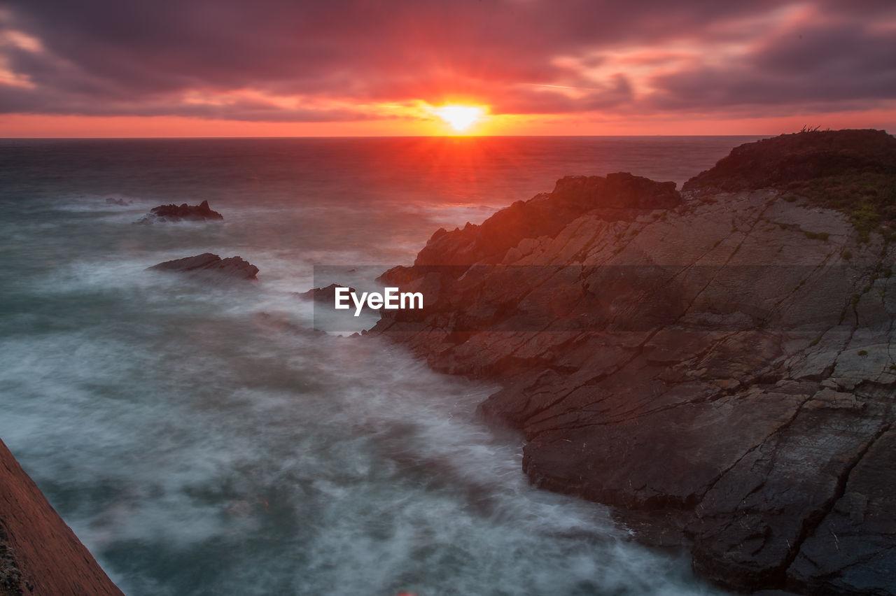 sky, beauty in nature, scenics - nature, sunset, cloud - sky, sea, orange color, tranquil scene, water, tranquility, idyllic, nature, sun, rock, no people, non-urban scene, horizon, horizon over water, rock - object, outdoors