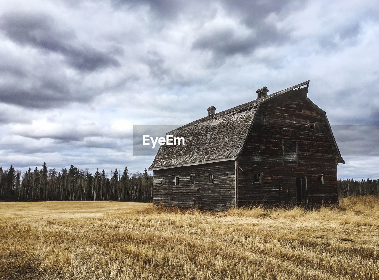 cloud - sky, sky, field, land, landscape, architecture, built structure, plant, grass, nature, abandoned, building exterior, environment, rural scene, day, old, no people, farm, building, deterioration, outdoors, ruined