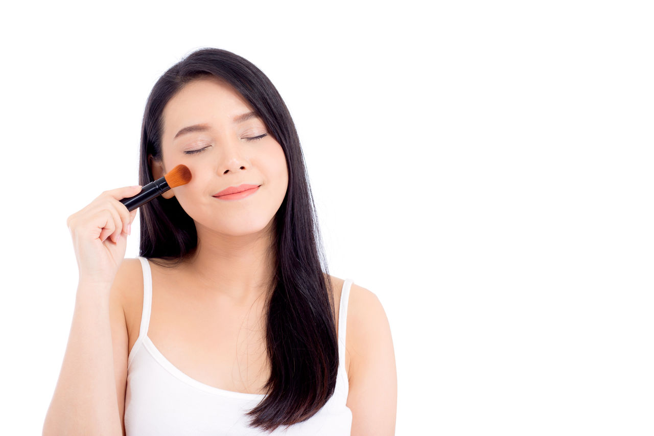 Beautiful woman with eyes closed applying make-up over white background