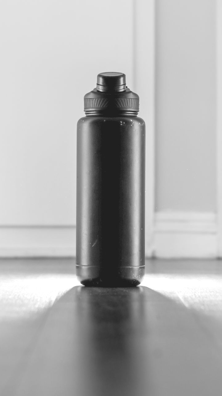 indoors, metal, still life, close-up, no people, table, selective focus, container, equipment, copy space, spray bottle, single object, can, aerosol can, day, flooring, shadow, pattern, alloy, wall - building feature, steel
