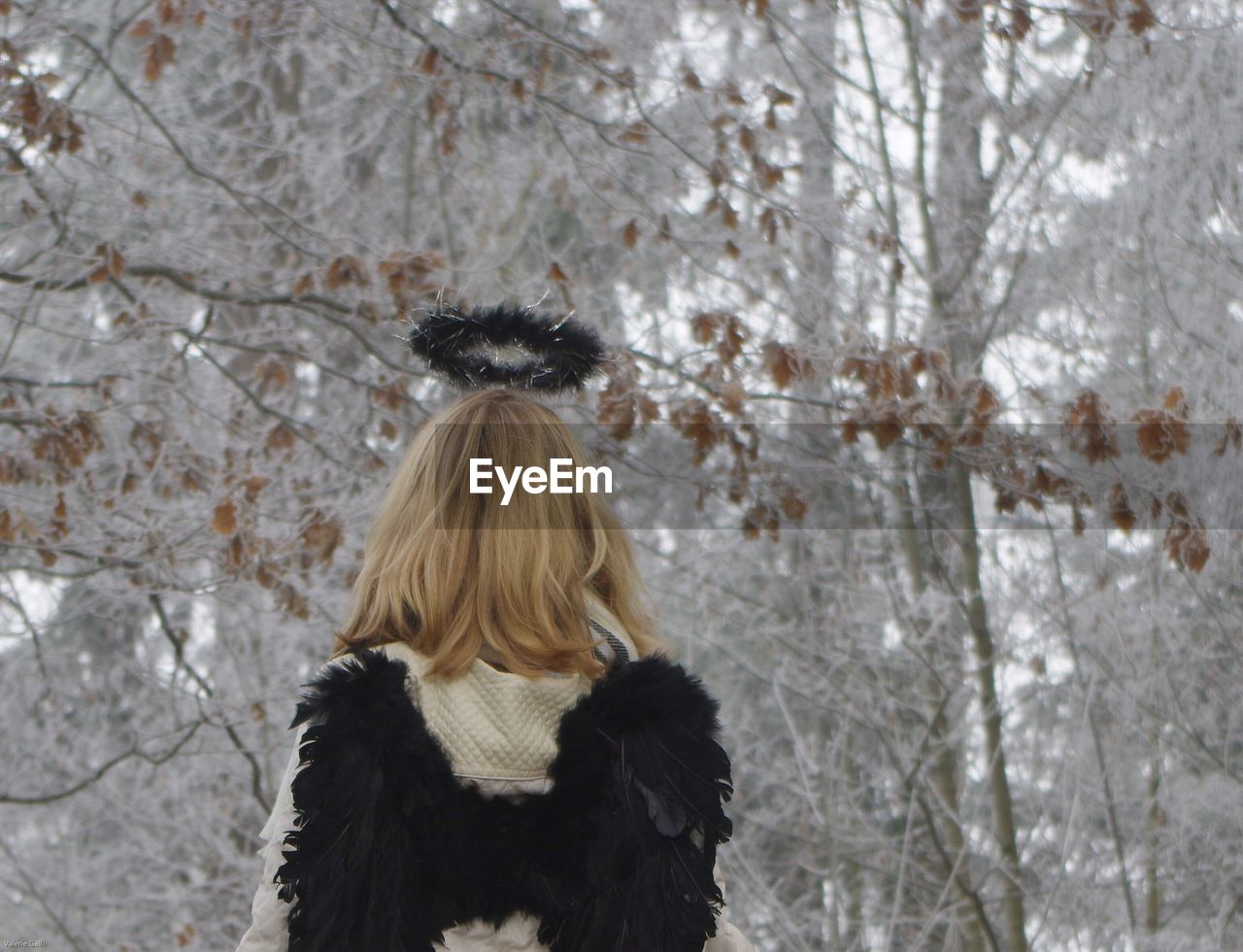Woman Against Snow Covered Bare Tree