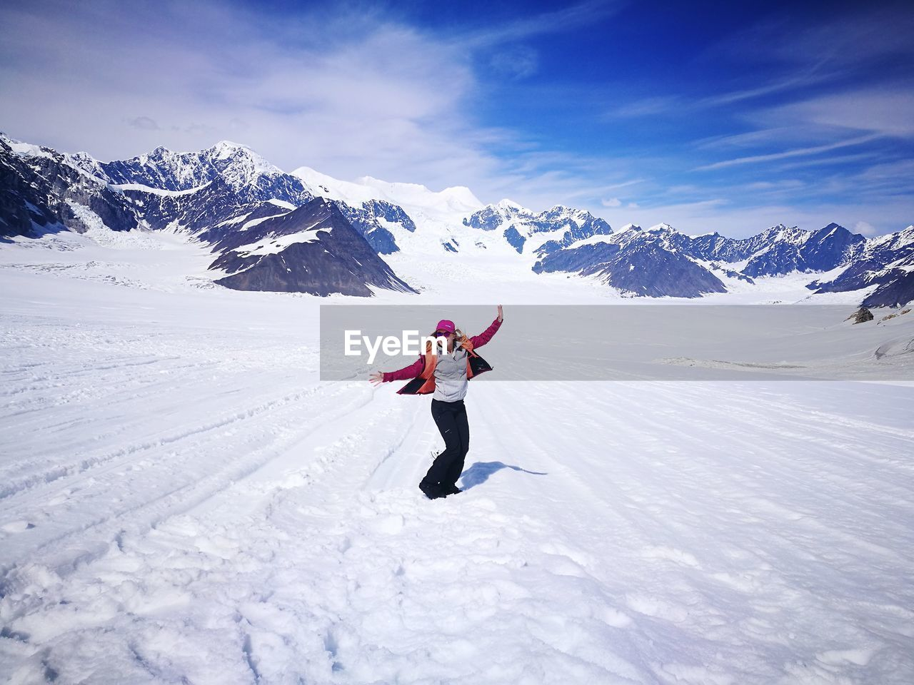 Happy woman with arms outstretched enjoying on snow covered field against mountains