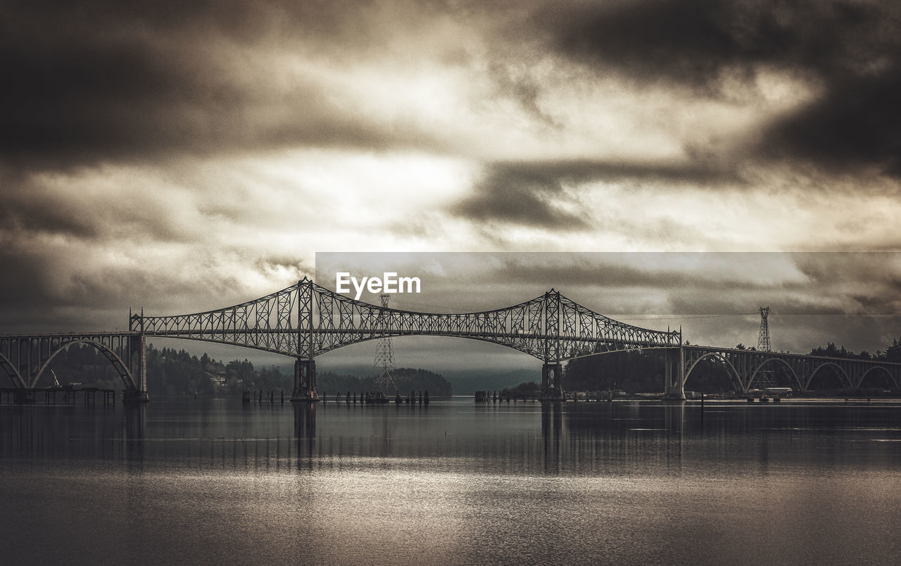cloud - sky, sky, bridge, connection, built structure, bridge - man made structure, architecture, water, river, waterfront, nature, engineering, transportation, reflection, outdoors, overcast, travel destinations, long