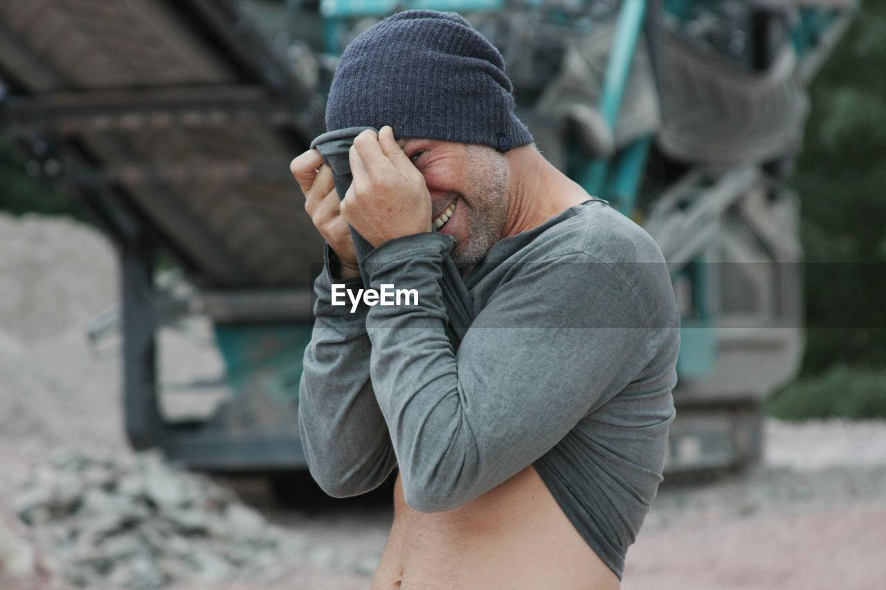 Portrait Of Man Hiding Behind His Shirt