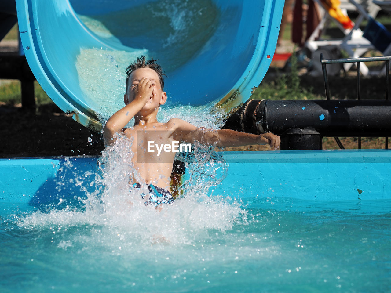 water, leisure activity, motion, fun, splashing, real people, one person, enjoyment, child, swimming pool, childhood, lifestyles, pool, men, day, nature, males, boys, water slide, mouth open, outdoors, inflatable, excitement, innocence