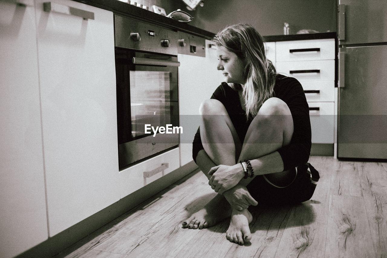one person, real people, indoors, full length, young adult, sitting, lifestyles, young women, flooring, leisure activity, home interior, women, wood, hardwood floor, looking, looking away, adult, hairstyle, contemplation, depression - sadness, beautiful woman