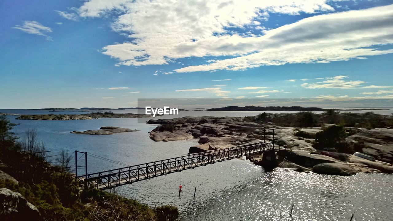 sky, water, bridge - man made structure, cloud - sky, connection, nature, high angle view, built structure, outdoors, day, architecture, river, scenics, beauty in nature, no people, tranquil scene, travel destinations, landscape, tree, horizon over water