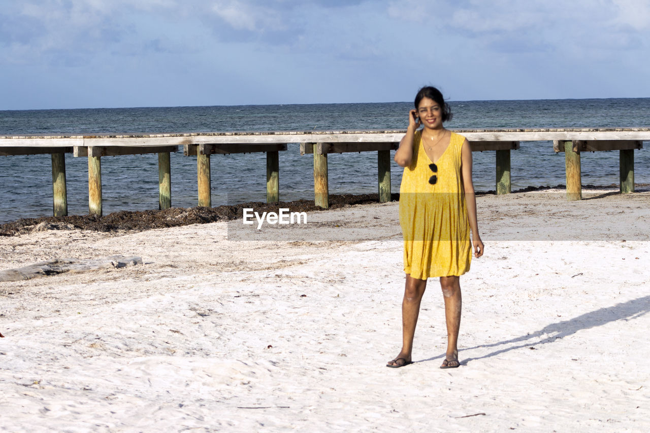 Full length of smiling woman standing at beach