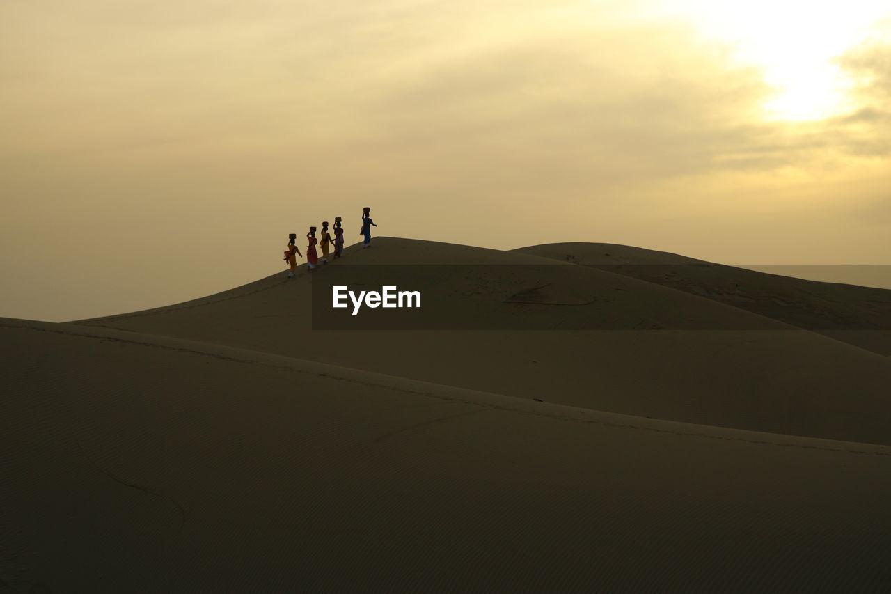 Silhouette Women Walking At Desert Against Sky During Sunset