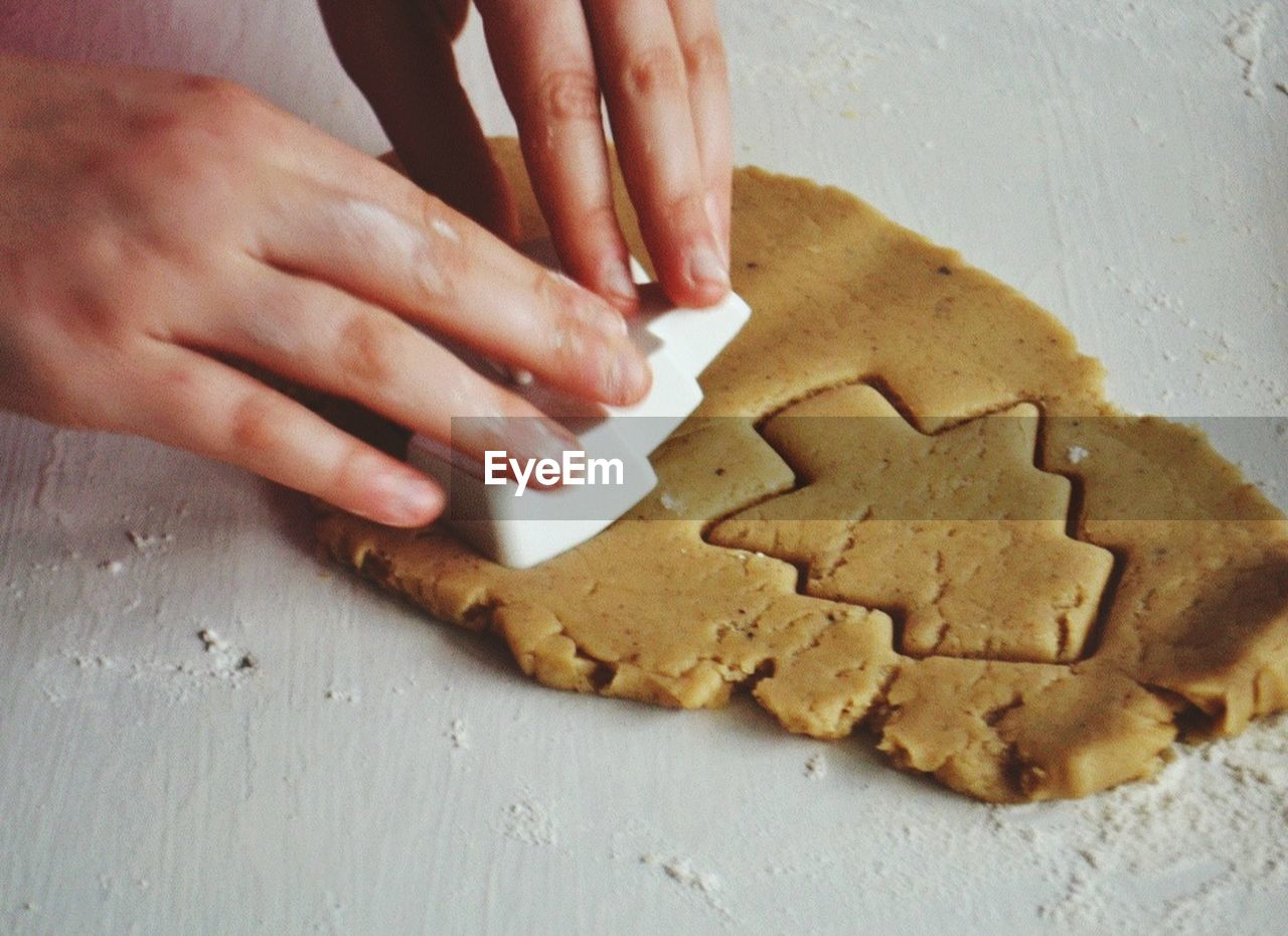 human hand, hand, food and drink, food, cookie, human body part, baked, indoors, one person, preparation, table, real people, sweet food, freshness, dough, preparing food, close-up, unrecognizable person, christmas, high angle view, body part, finger, gingerbread cookie