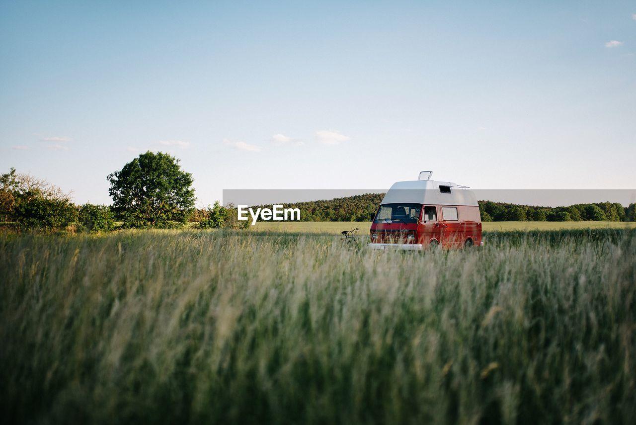 Motor Home On Grassy Field Against Sky
